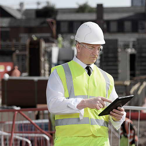 man using digital form on tablet on construction site